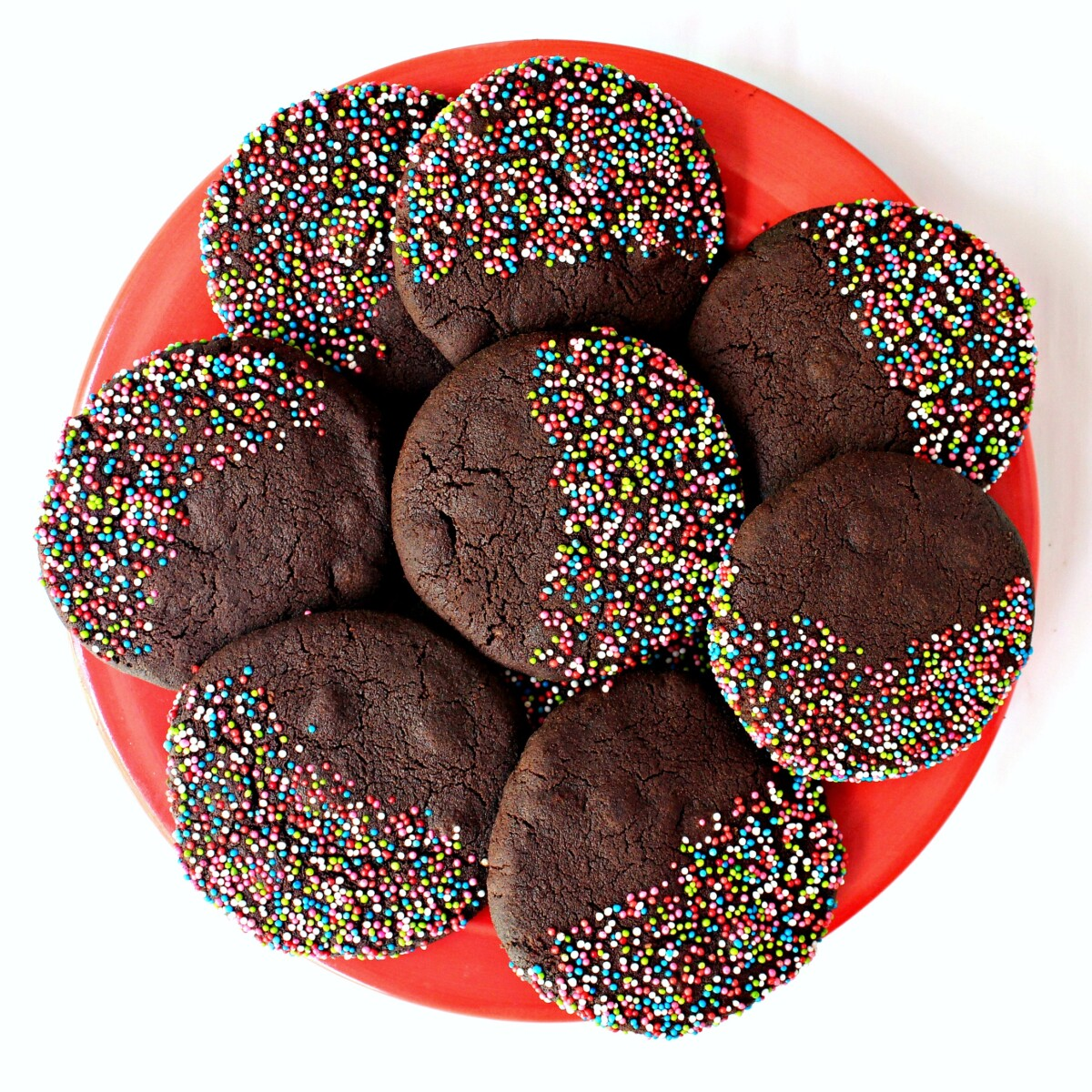 Chocolate cookies with nonpareil sprinkles on a red serving plate.