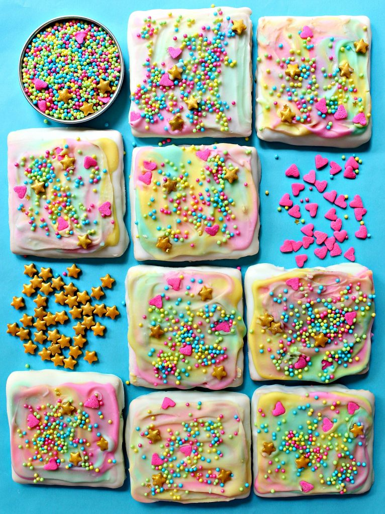 Unicorn Sprinkle Chocolate Covered Graham Crackers are square grahams dipped in white chocolate, swirled with pastel colored chocolate, and sprinkled with pastel nonpareils, pink heart sprinkles, and gold star sprinkles. Here they are lying in rows against an aqua background