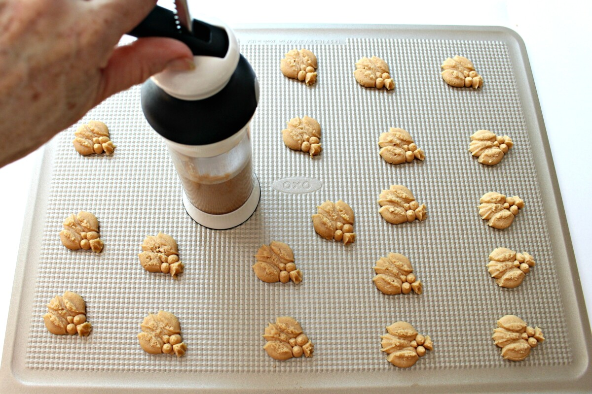 Using cookie press to add owl cookies to a baking sheet.