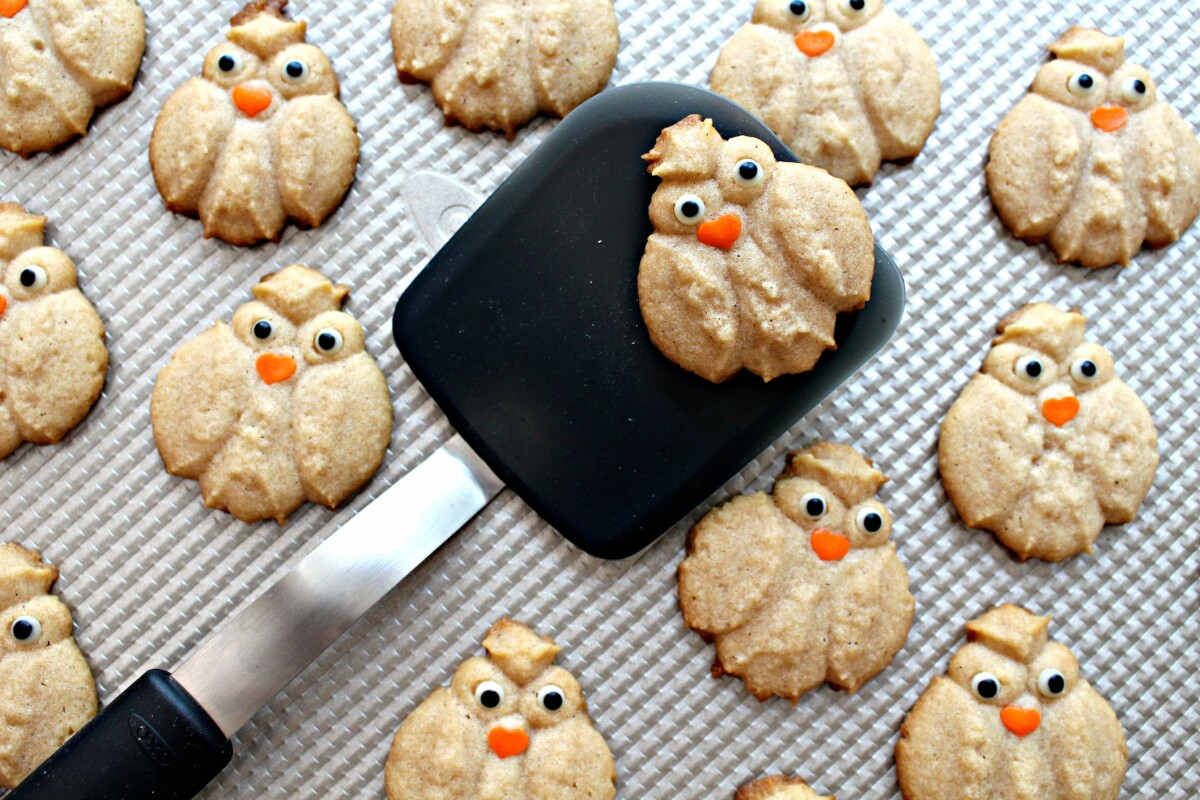 Baked Cinnamon Spritz Owl Cookies being removed from baking sheet with a black spatula.