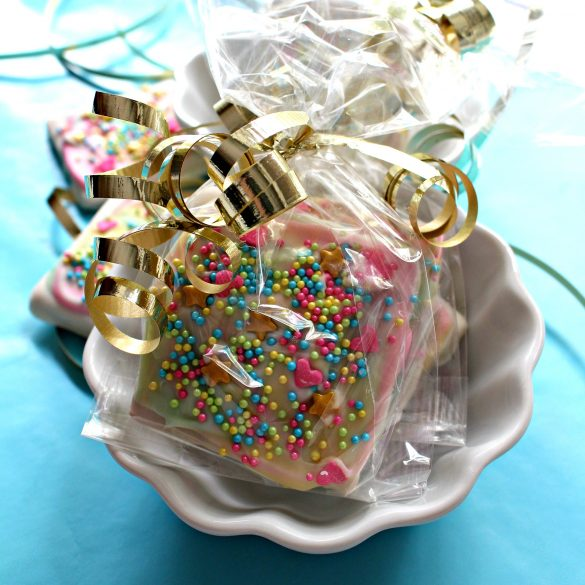 The decorated cookies are wrapped for gifting in clear cellophane gift bags tied with metalic gold curling ribbon.