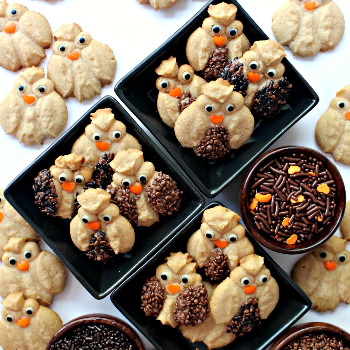 Decorated Cinnamon Spritz Owl Cookies in small black bowls with bowls of decorating sprinkles.