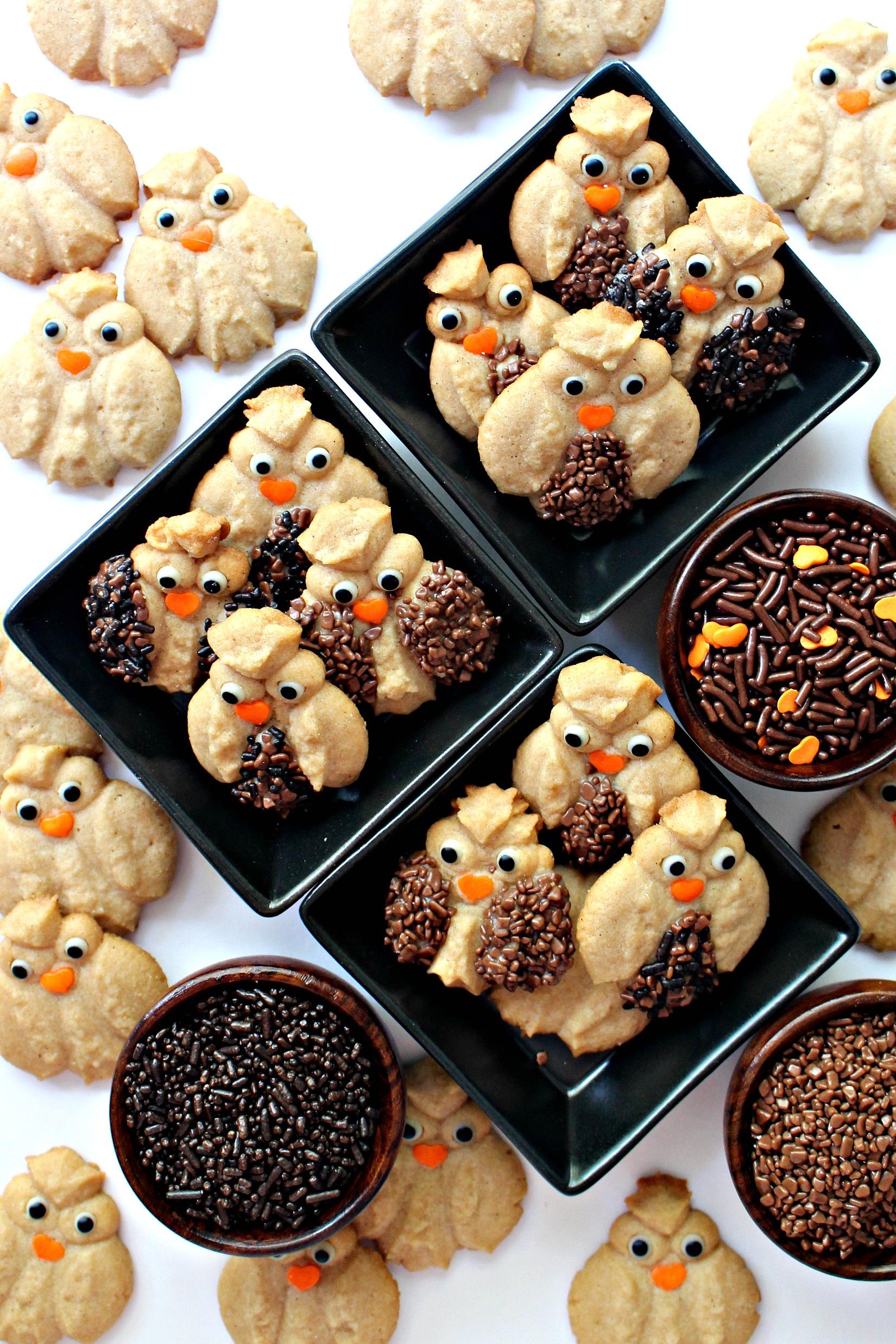 Cinnamon Spritz Owl Cookies with added chocolate sprinkles feathers, candy eyes, and orange sprinkle beaks.