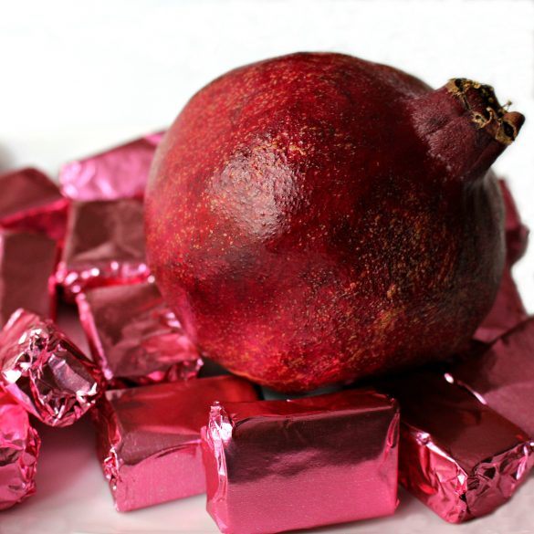 Pomegranate Caramels wrapped in pink foil surround a pomegranate and make great Rosh Hashanah gifts