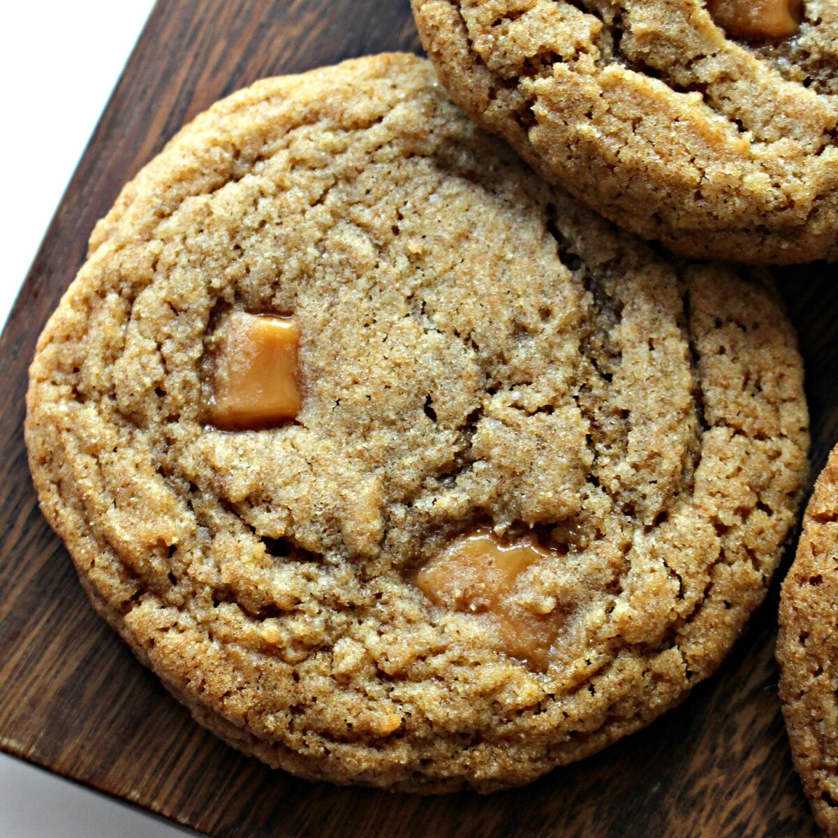 Closeup of cookie showing chunks of caramel and golden brown, crinkled top.