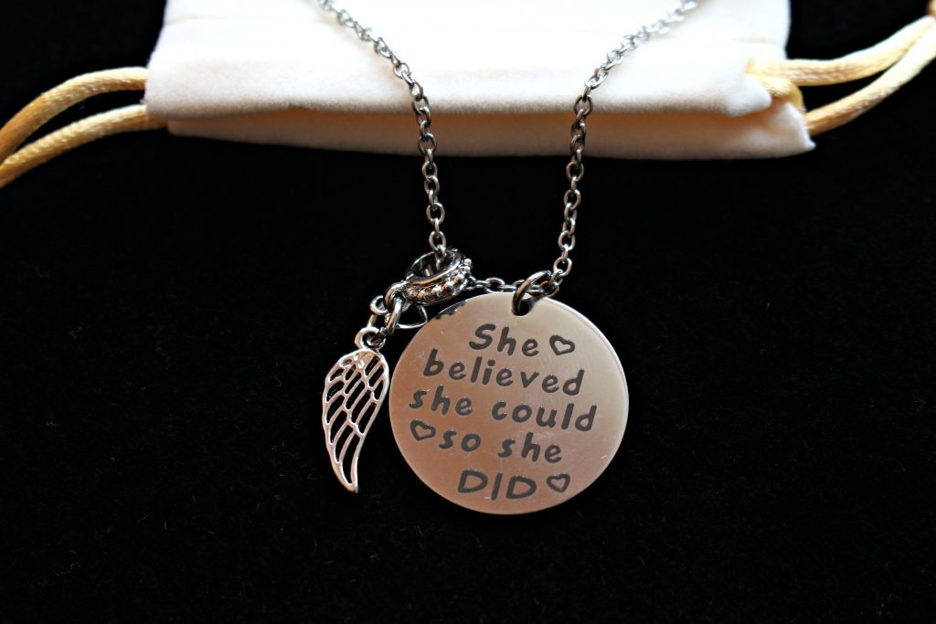 "Necklace with silver colored disc charm with motivational quote, ""She believed she could so she did"" and an angel wing charm on a silver link chain."