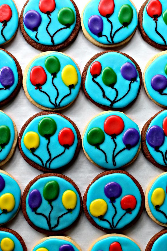 Balloon Sugar Cookies with a sky blue icing background and 3 colored, circle balloons with black strings on each cookie.
