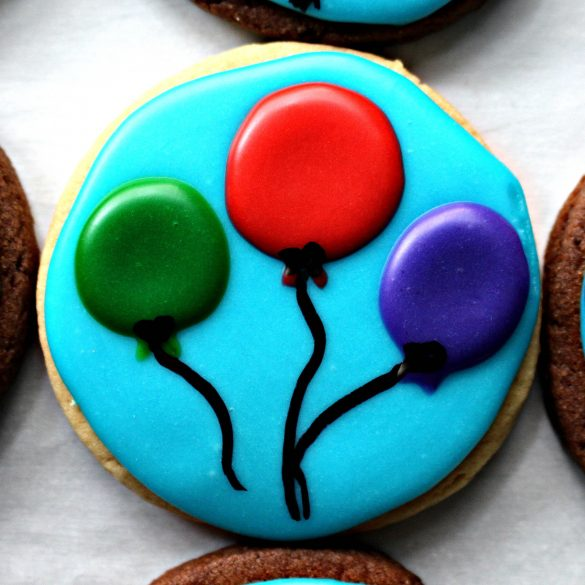 Closeup of round sugar cookie decorated with light blue icing and three balloons