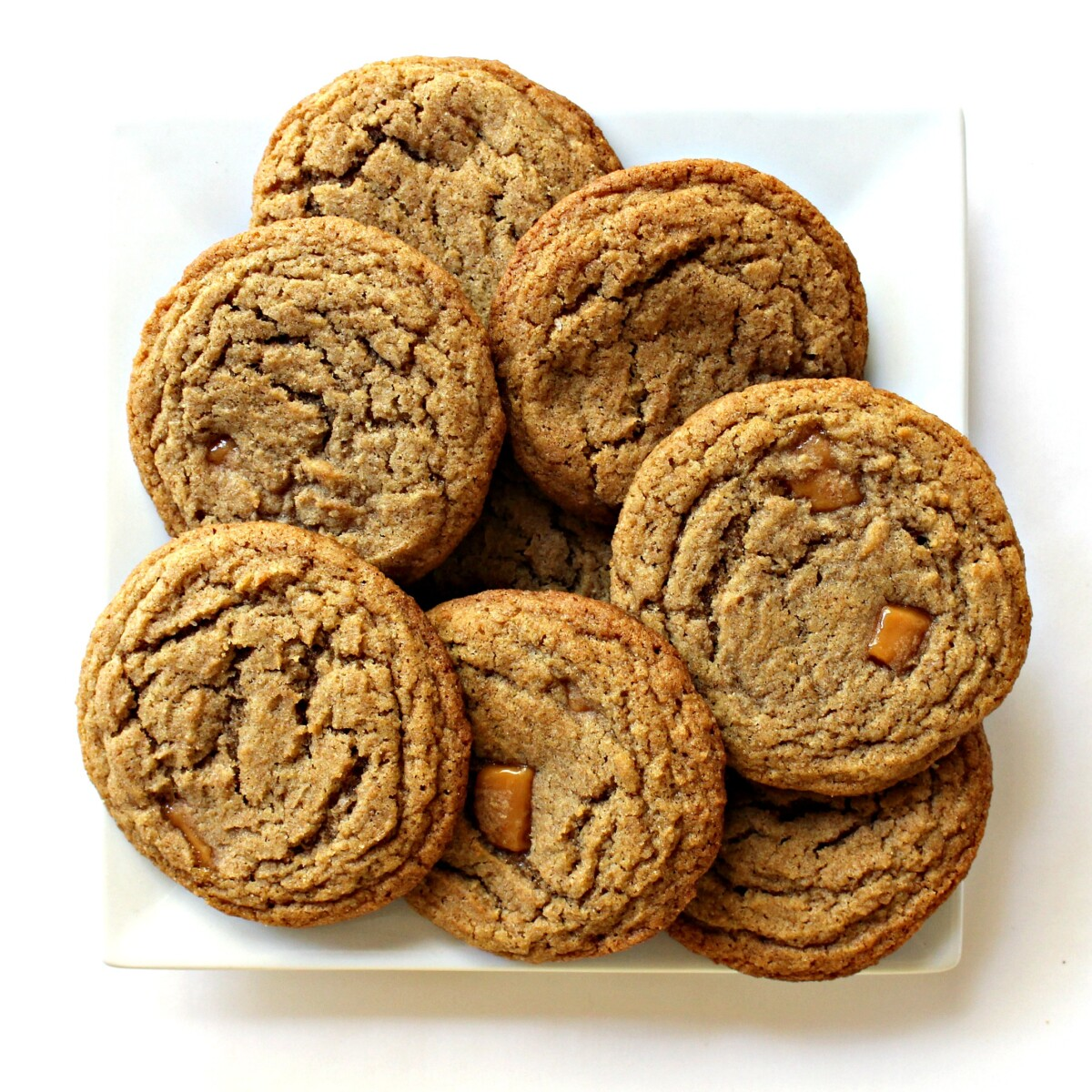 Thin, golden brown cookies with crinkled tops and caramel chunks on a square white plate.