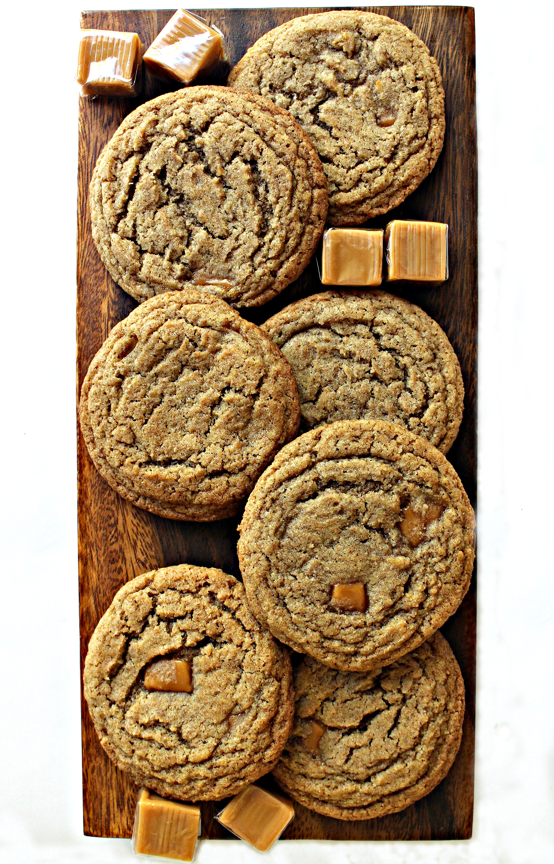 Thin, crinkled Whole Wheat Caramel Cookies on a wooden cutting board with caramel squares.
