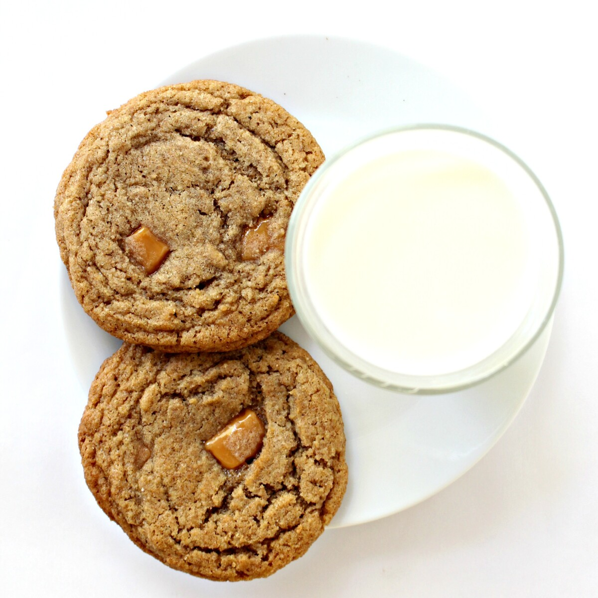 Overhead photo of two golden brown, crinkled cookies on a plate with a glass of milk.