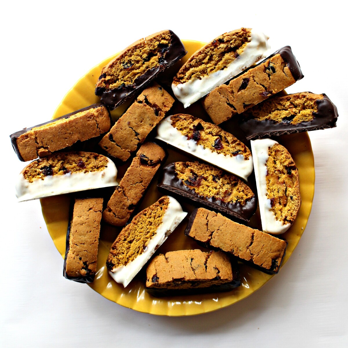 Chocolate dipped Pumpkin Biscotti decoratively arranged on a round, yellow serving platter.