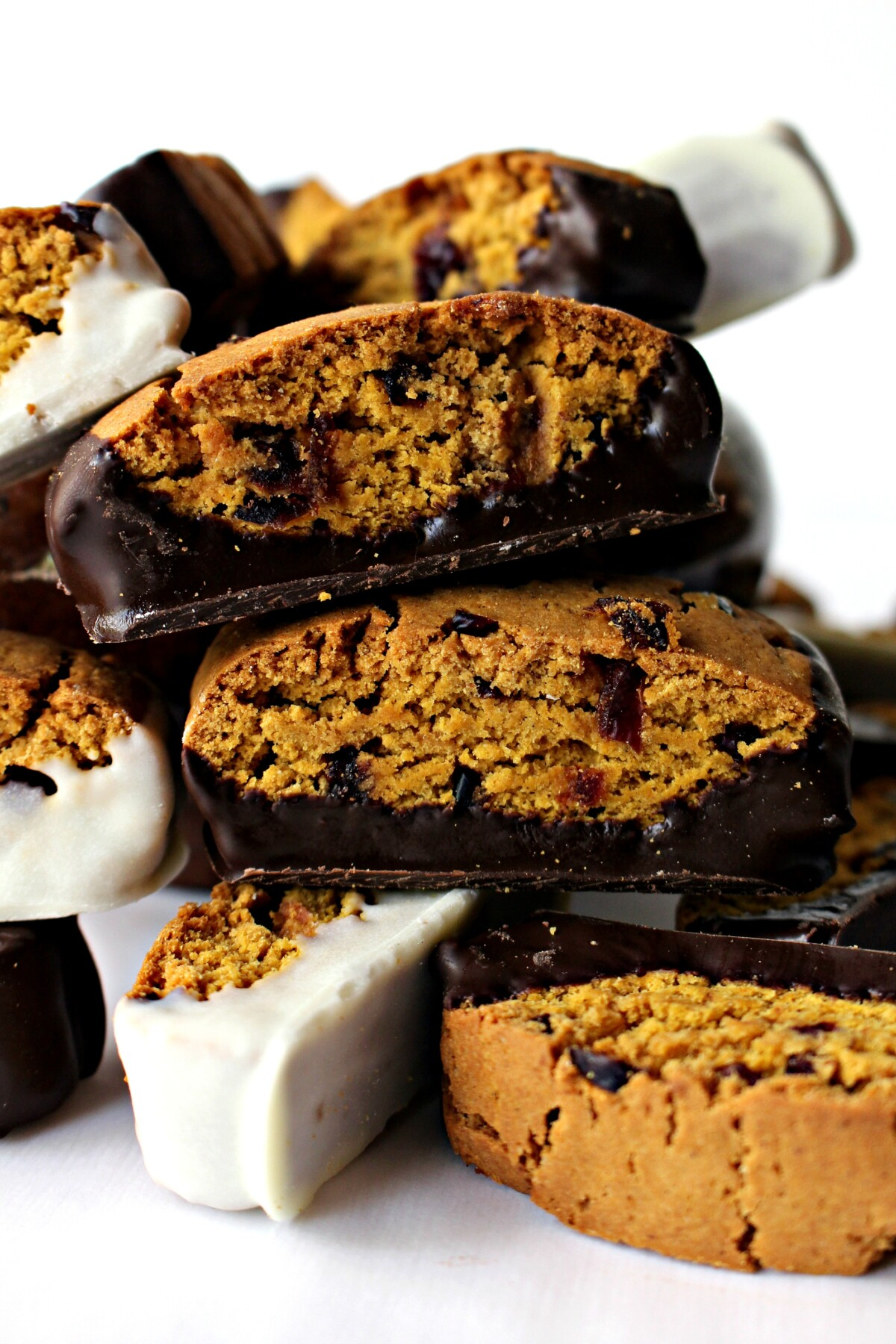 Pumpkin Cranberry Biscotti, speckled with dried cranberries, and bottoms dipped either in dark or white chocolate.