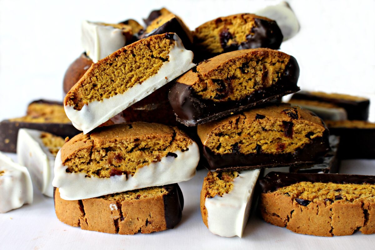 Pile of orange colored Pumpkin Cranberry Biscotti, with bottoms dipped in white or dark chocolate.