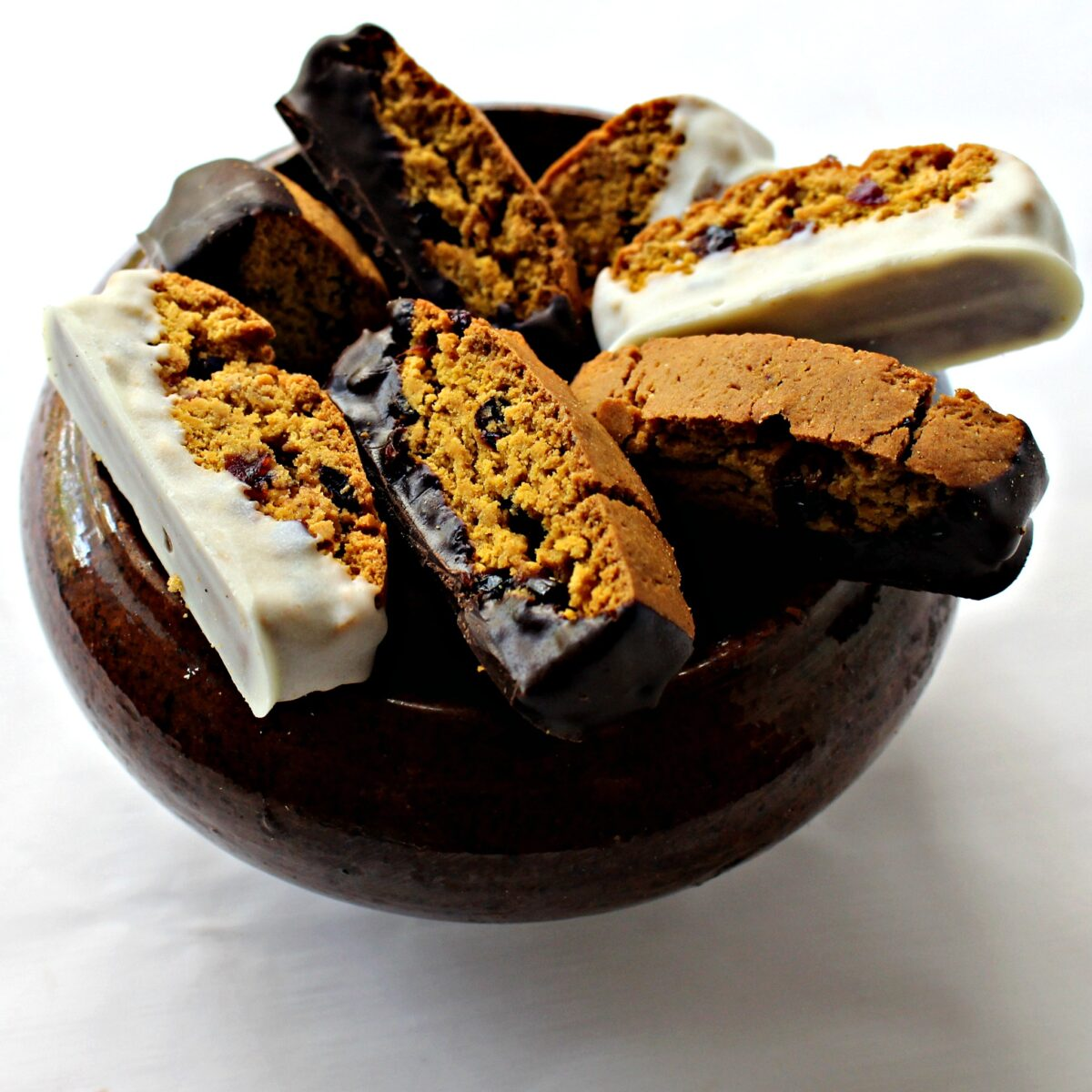 Biscotti in a brown pottery bowl with white chocolate or dark chocolate dipped bottoms.