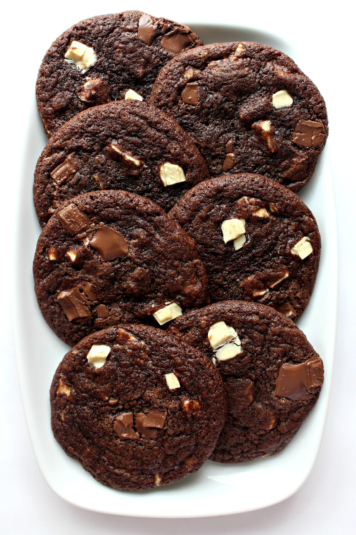 Chocolate cookies with white and milk chocolate chunks on top on a white serving platter.