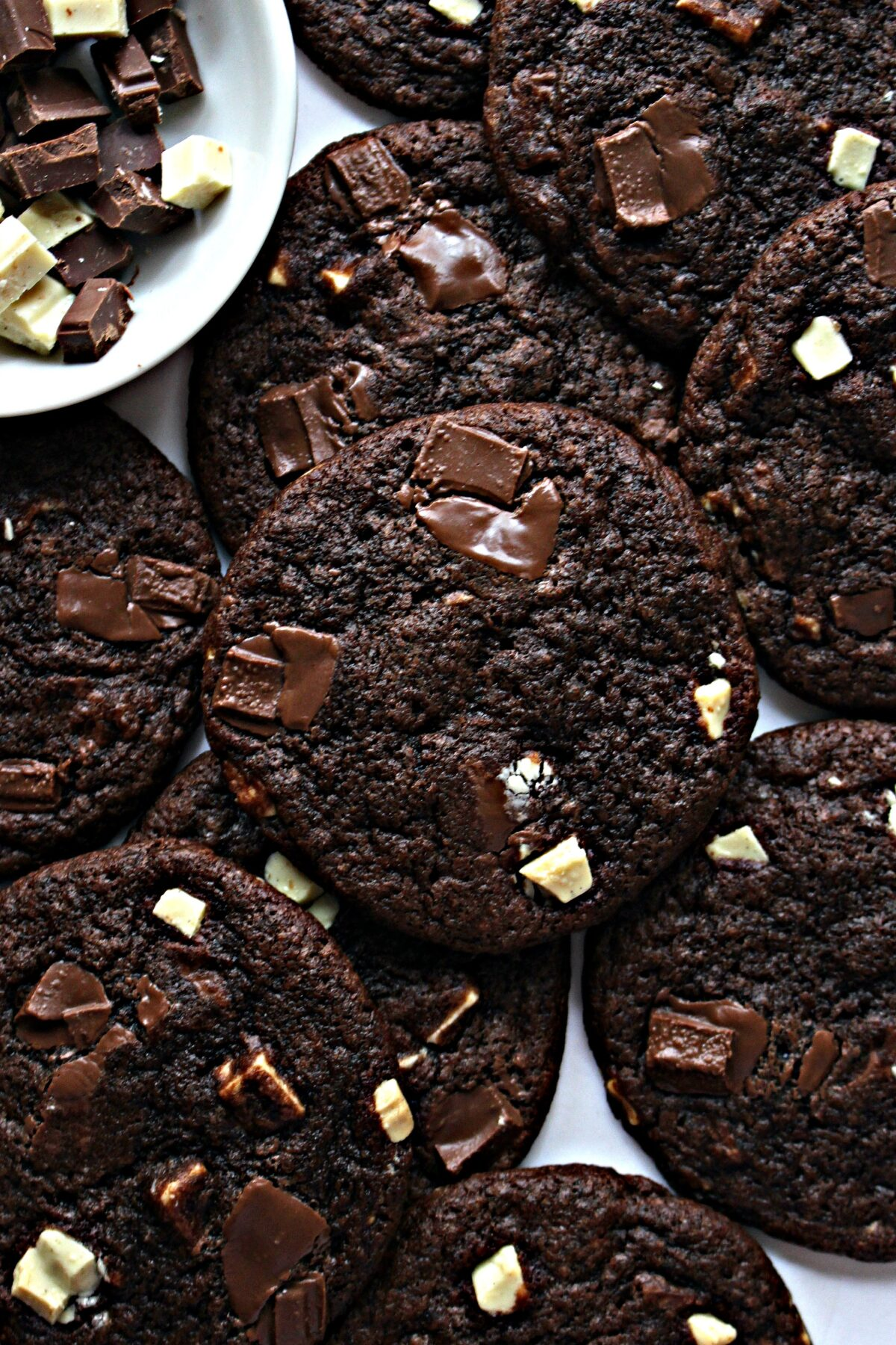 Dark chocolate brown Chocolate Chunk Cookies with pieces of dark and white chocolate on top.