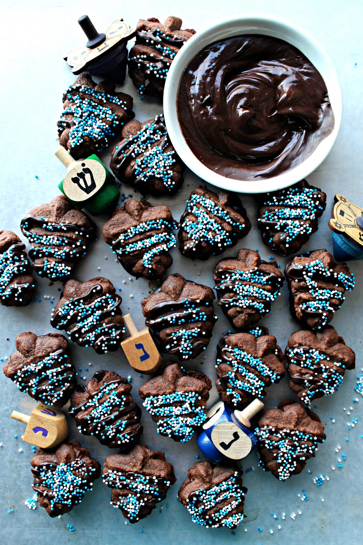 Chocolate cookie press cookies shaped like dreidels, sandwiched with chocolate, sprinkled with blue and white nonpareils.