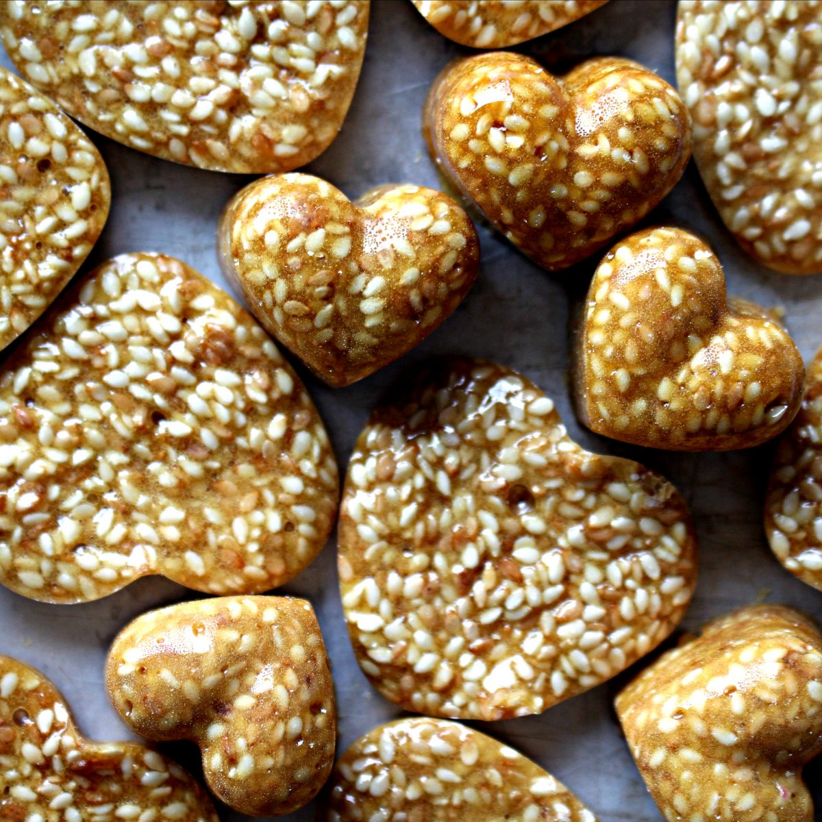 Closeup of shiny, golden brown heart shaped brittle pieces full of sesame seeds.