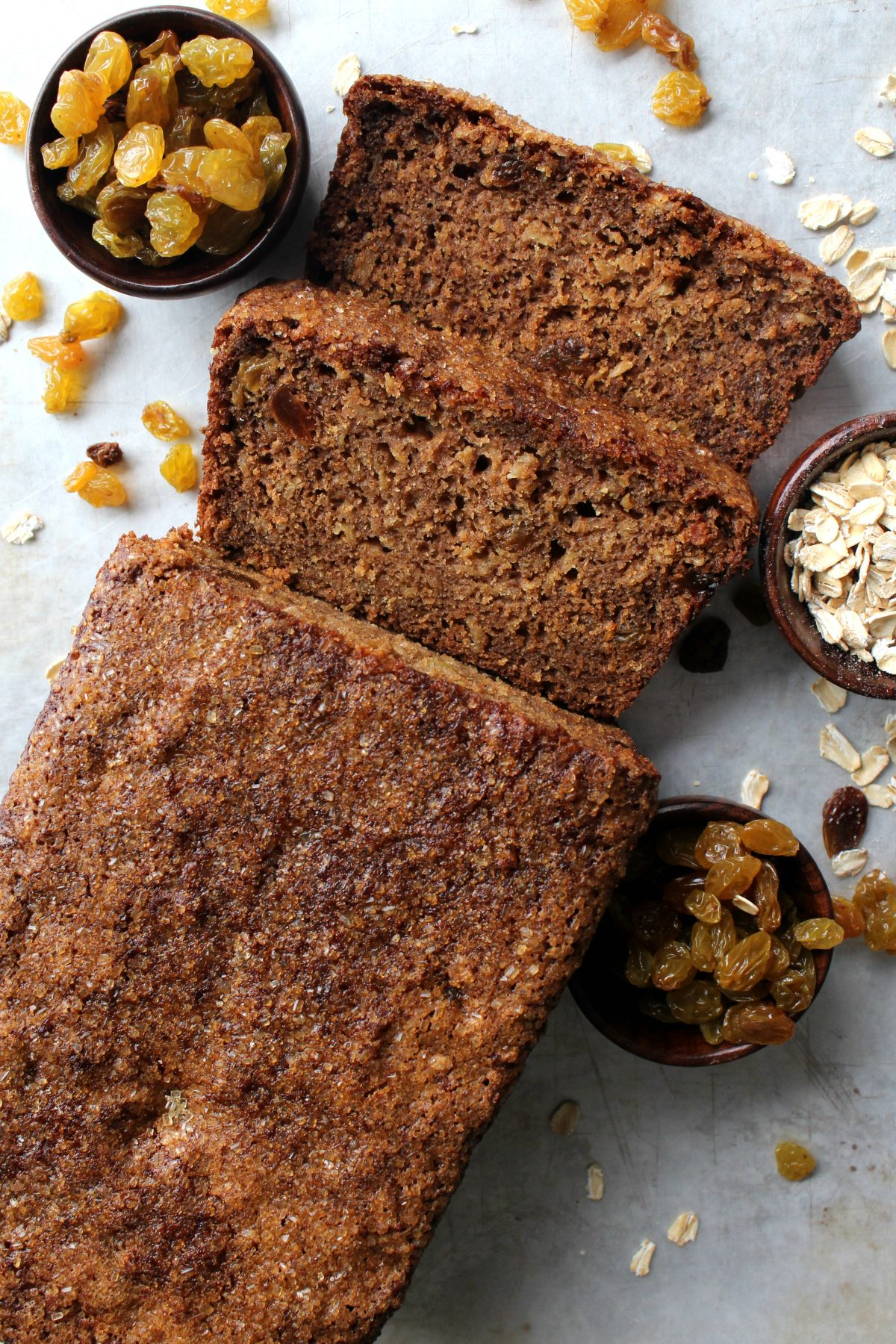 Oatmeal Raisin Quick Bread with two cut slices with little bowls of raisins and oatmeal.