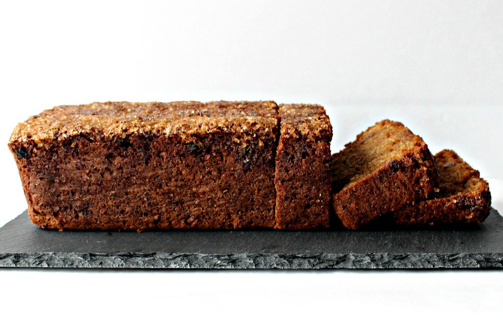 side view of Oatmeal Raisin Quick Bread on a slate platter with a few slices cut on the right side