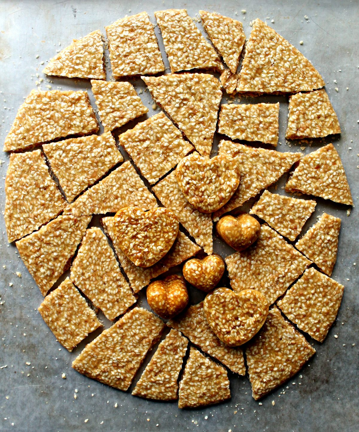 A large circle of Honey Sesame Brittle broken into shards and some heart molded brittle.
