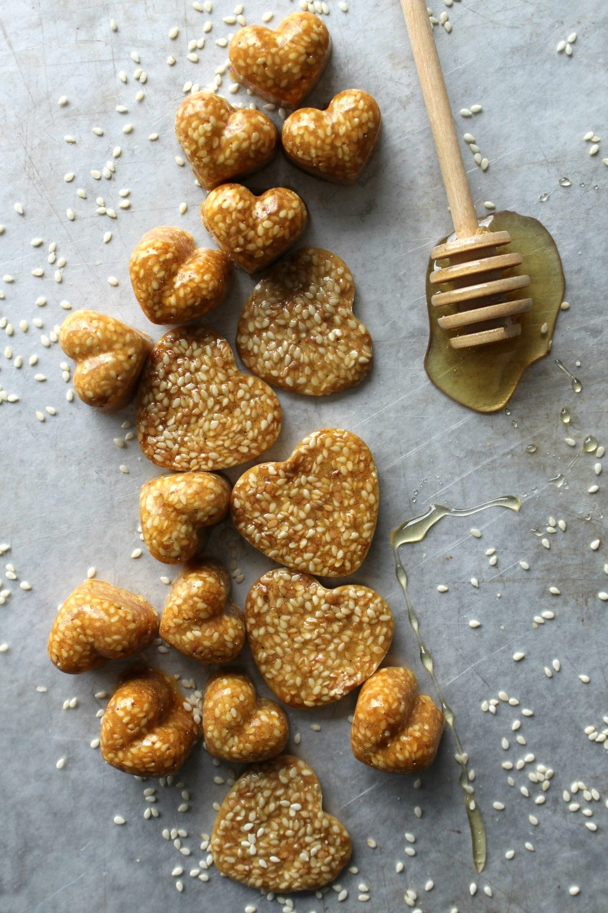 Heart shaped Honey Sesame Brittle candies on a gray background sprinkled with sesame seeds and honey.