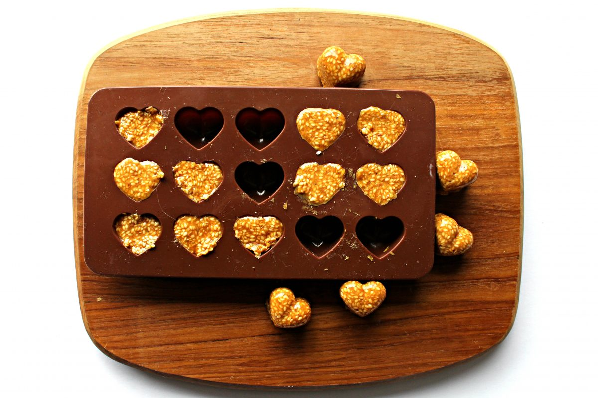 Brown silicone heart mold filled with brittle on a wooden cutting board.
