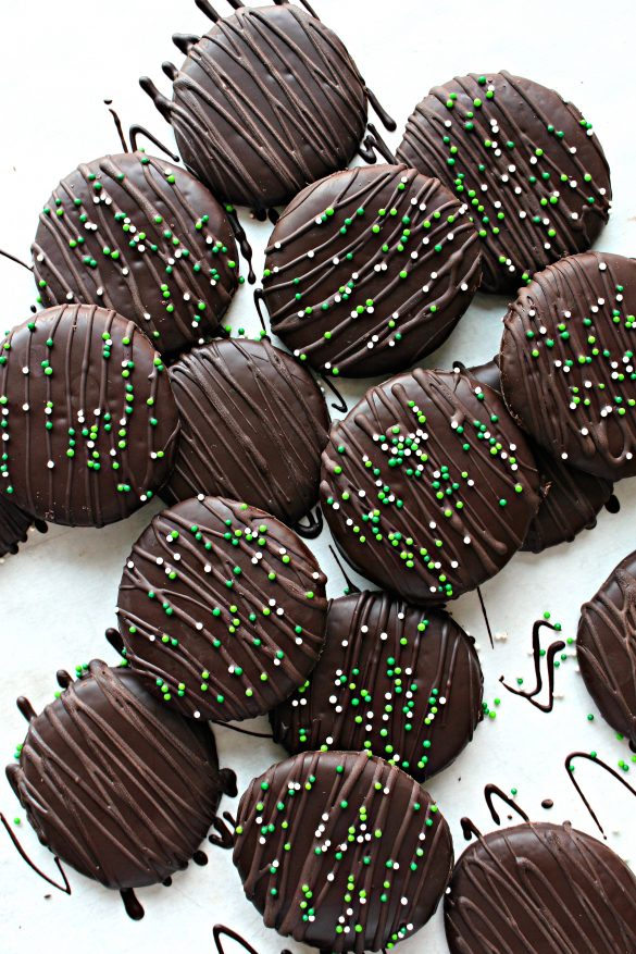 Chocolate Covered Chocolate Mint Cookies are decorated with chocolate zigzags and green and with nonpareil sprinkles.