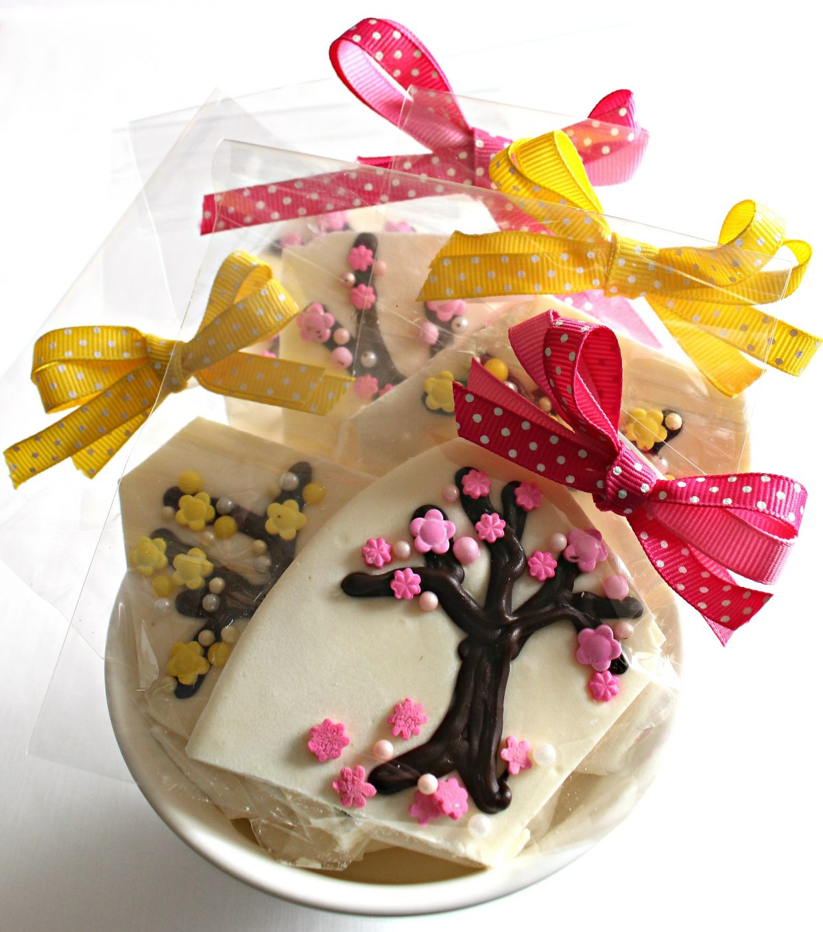 Spring Blossom White Chocolate Bark cut into pieces in cellophane bags with bows for gifting.