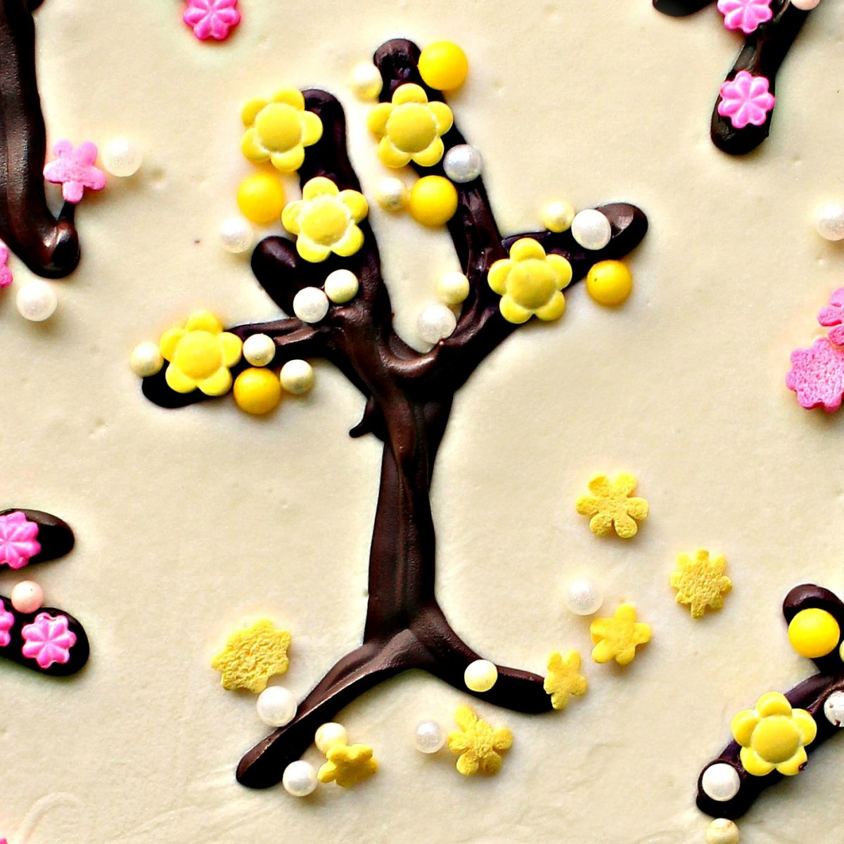 Closeup of piped chocolate tree trunk with yellow flower sprinkles and ball sprinkles.