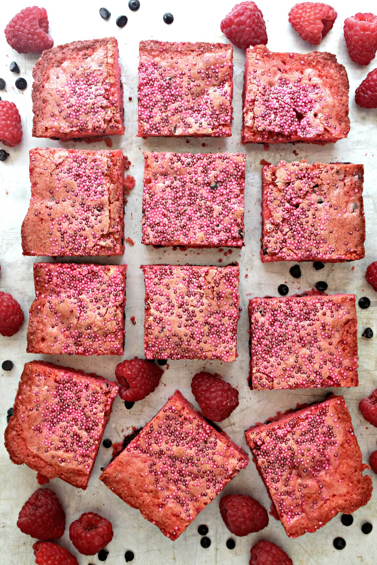 Raspberry Chocolate Chip Bars cut into squares on background sprinkled with chocolate chips and raspberries.