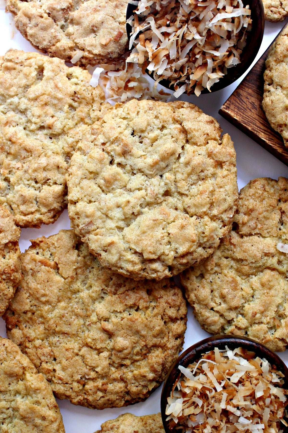 Roasted Coconut Crunch Cookies, thin with a crackled tops, with bowls of toasted coconut.