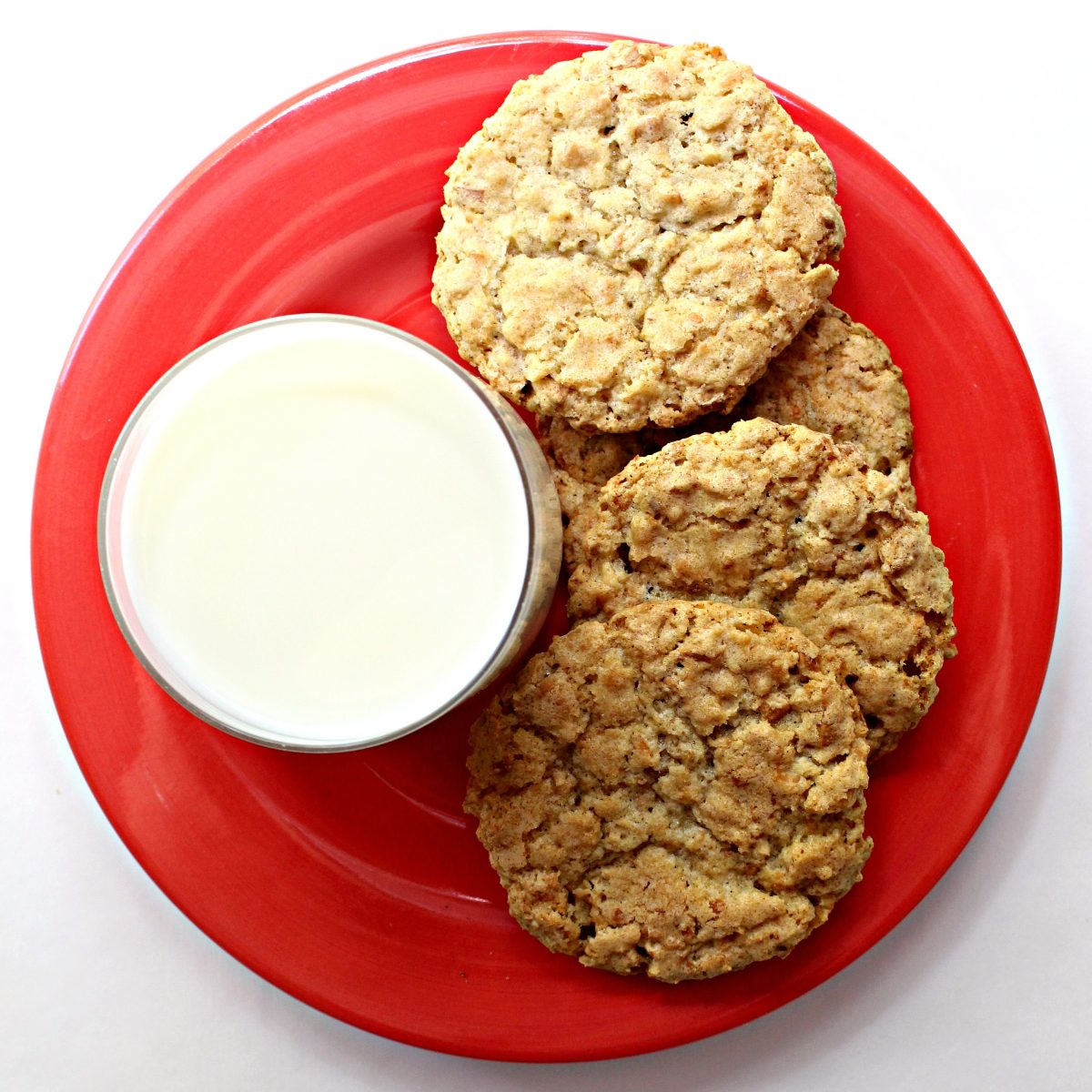 Roasted Coconut Crunch Cookies on a red plate with a glass of milk.
