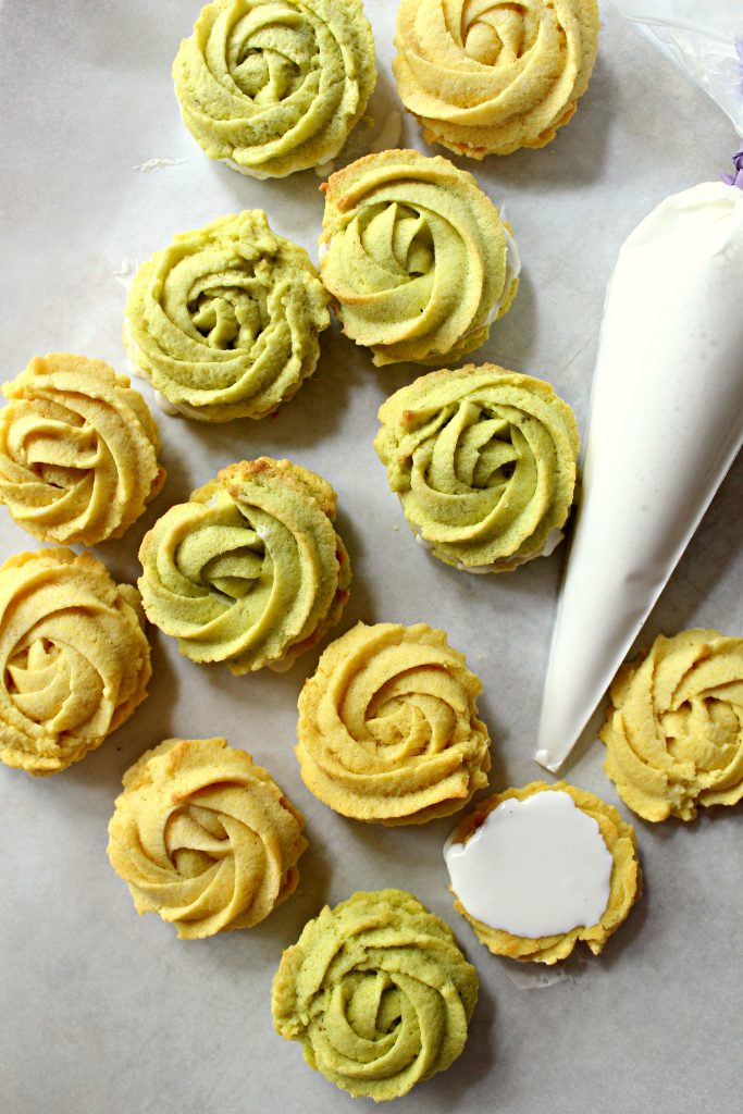 Lemon and Lime Butter Cookie Rosettes on gray background with a piping bag of icing.