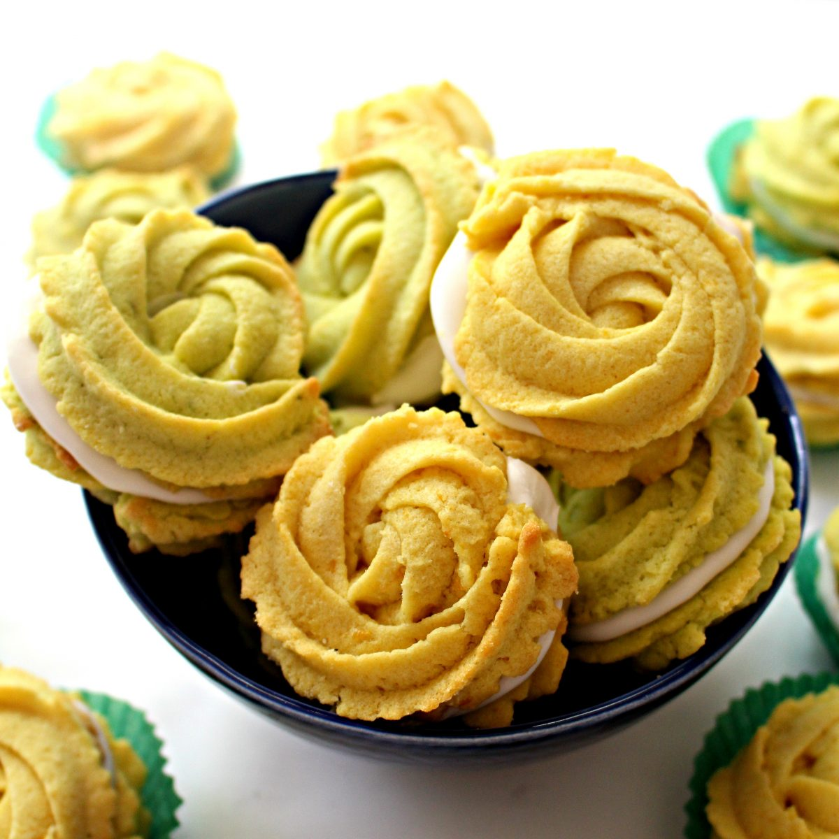 Close up of lemon and lime cookie rosettes sandwiched with white icing in a blue bowl.