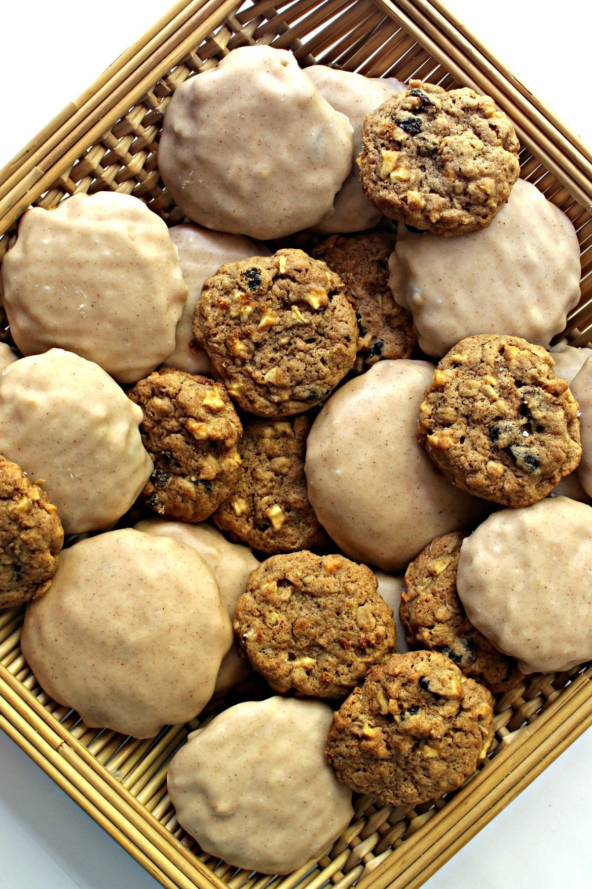 Apple Raisin Oatmeal Cookies, some plain and some iced, in a square basket.