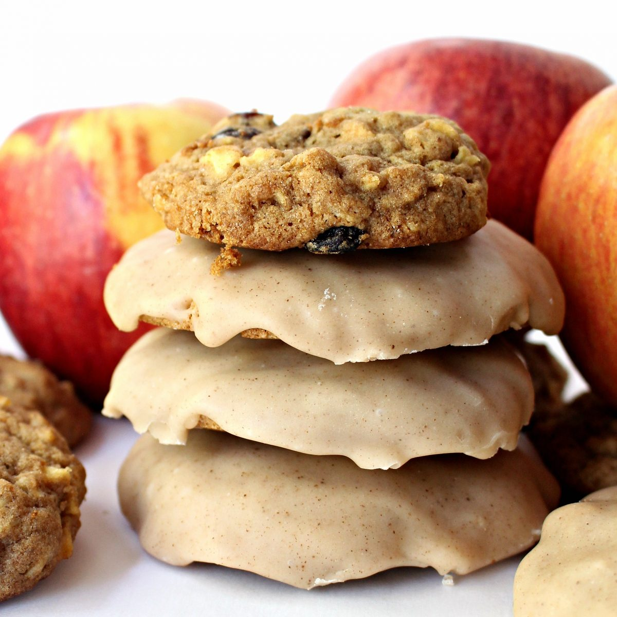 A stack of cookies with three iced and one plain.