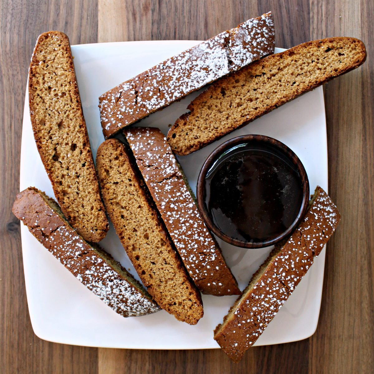 Biscotti on white plate with a bowl of honey.