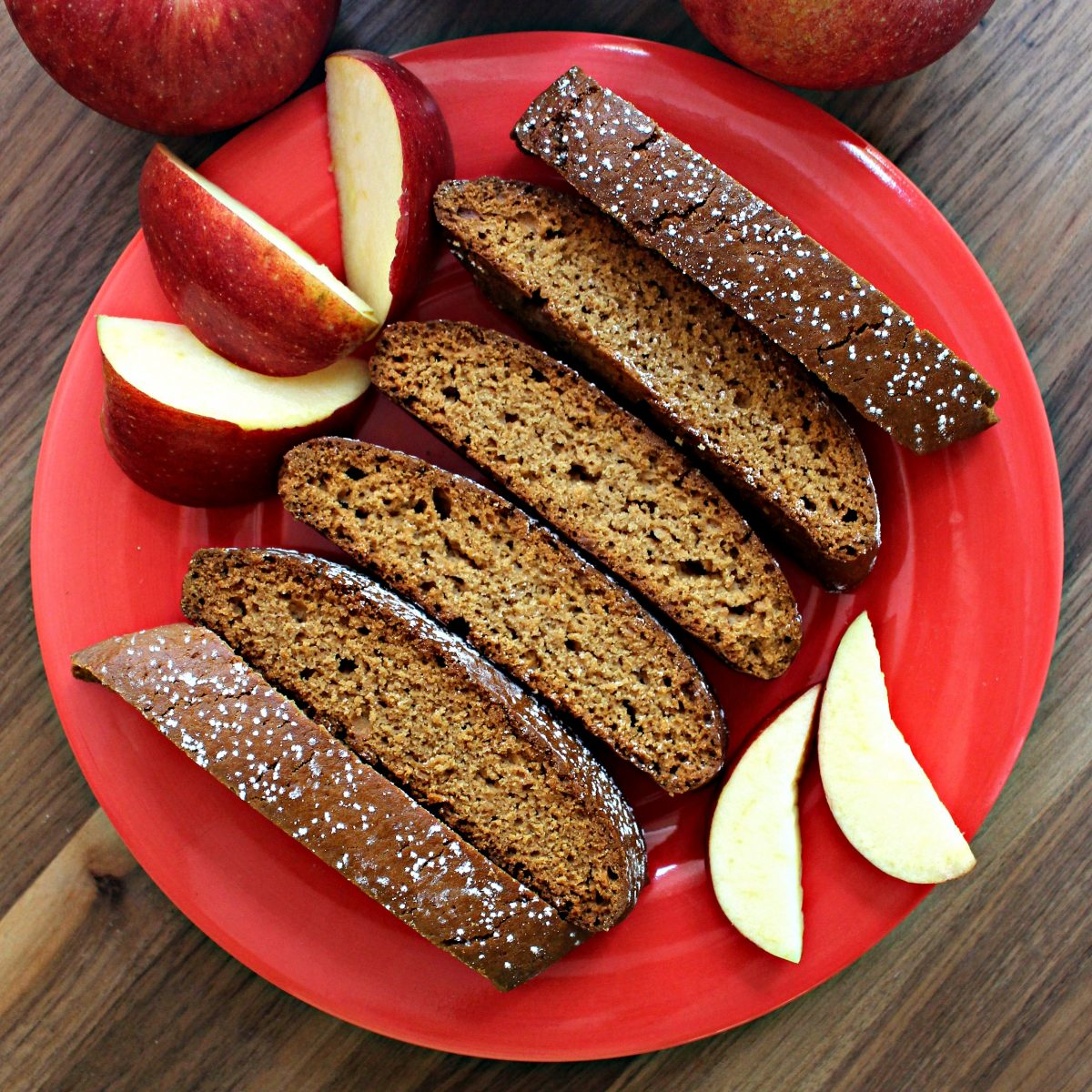 Biscotti on a red plate with apple slices.