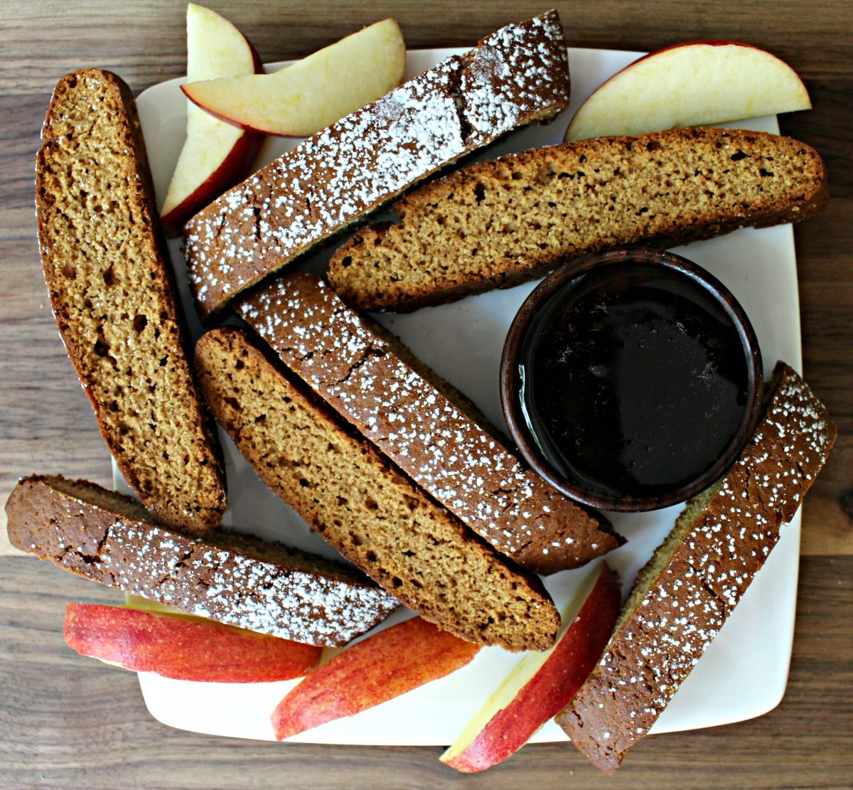 Overhead view of biscotti, apple slices, and a bowl of honey on a white plate.