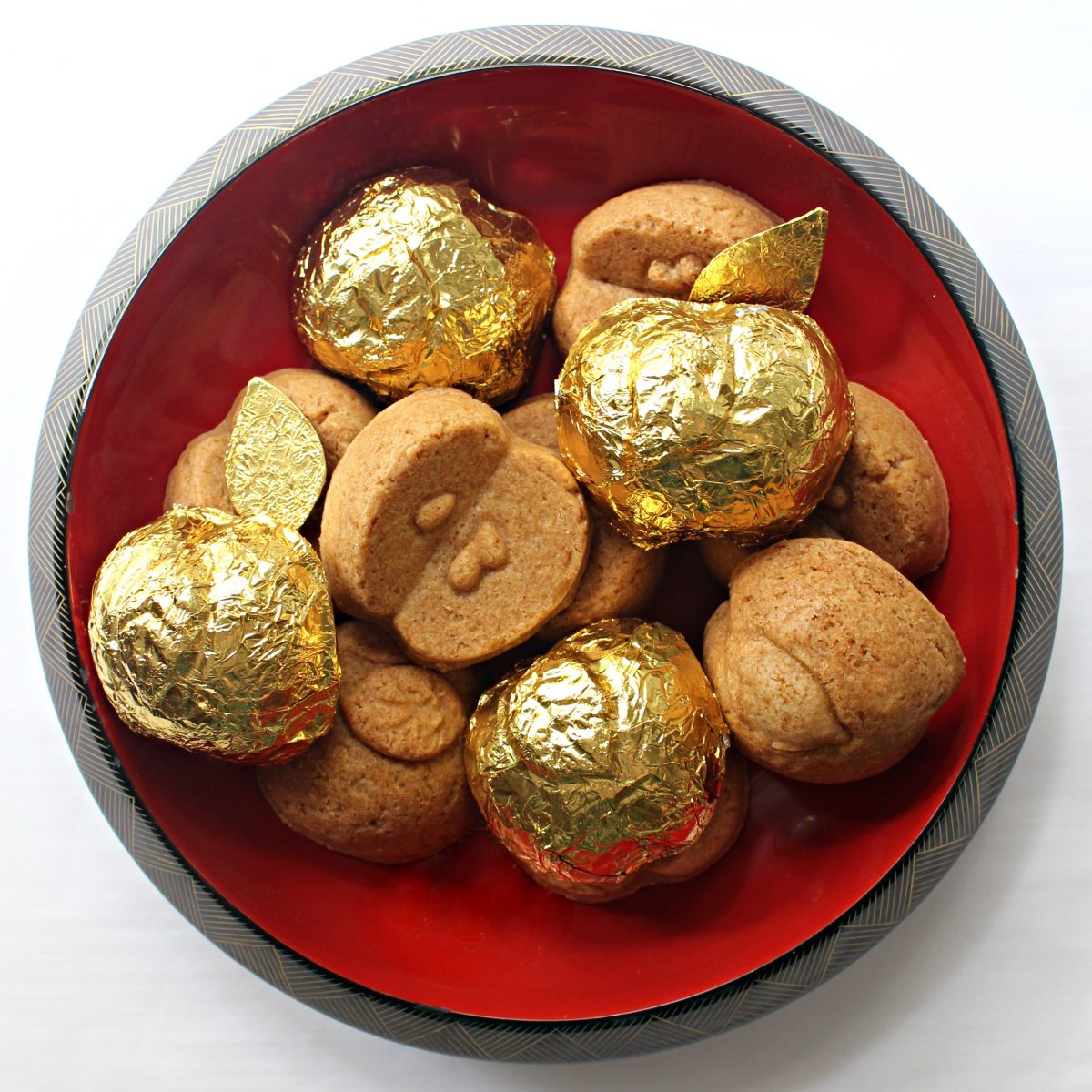 Apple shaped cookie-cakes, some wrapped in gold foil, inside a red laquered bowl.