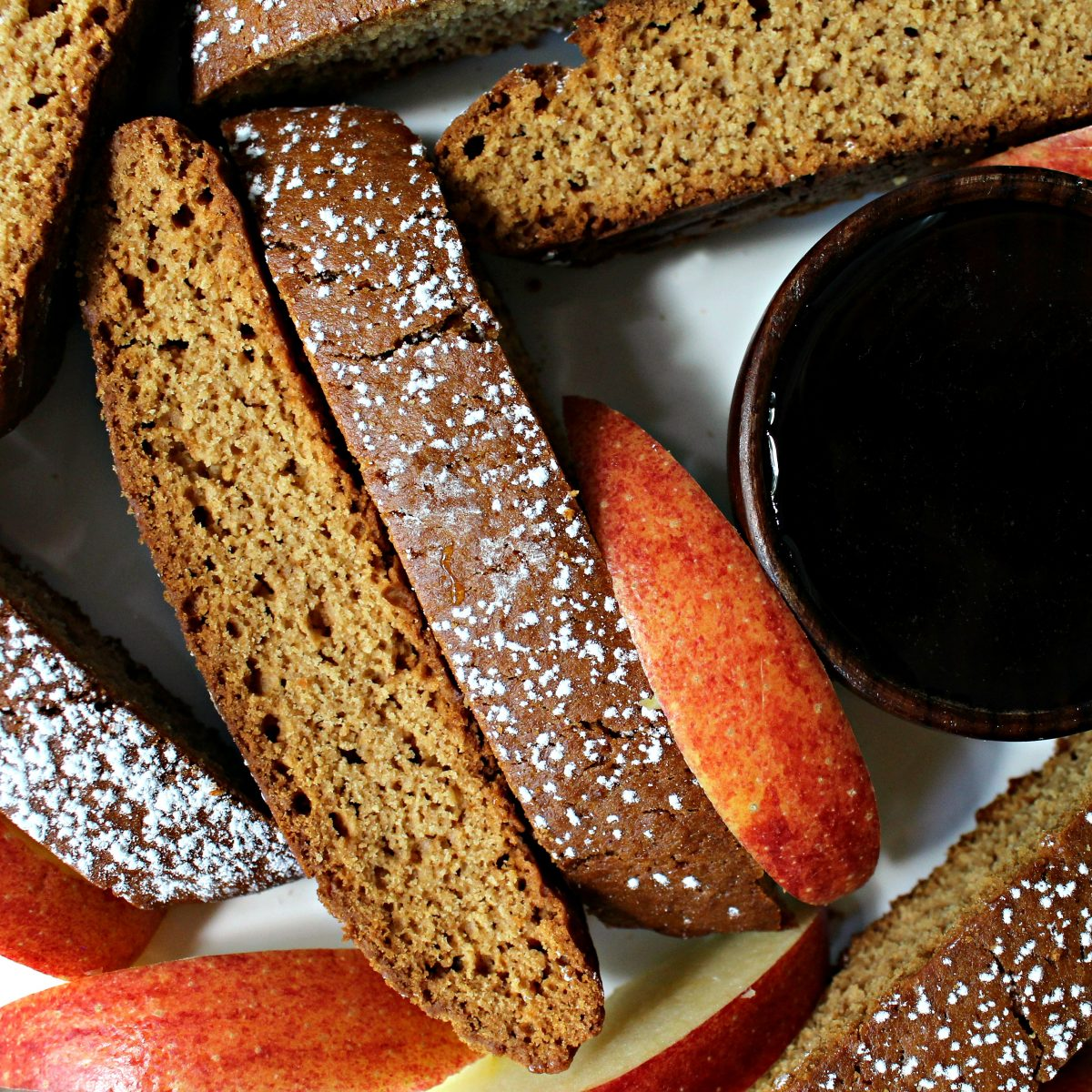 Closeup of biscotti and apple slices next to a bowl of honey.