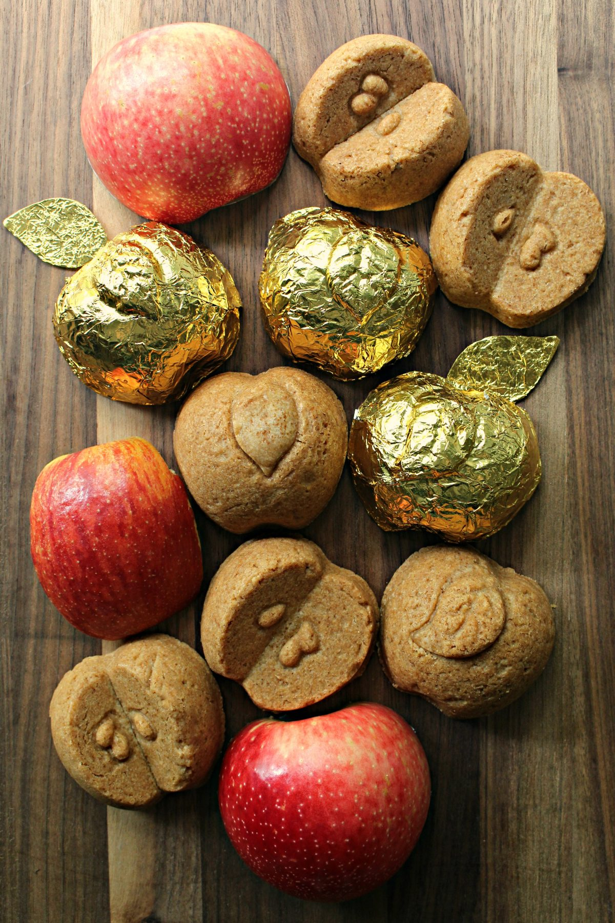 Apple shaped cakelets, three wrapped in gold foil, on wood cutting board with sliced apples.