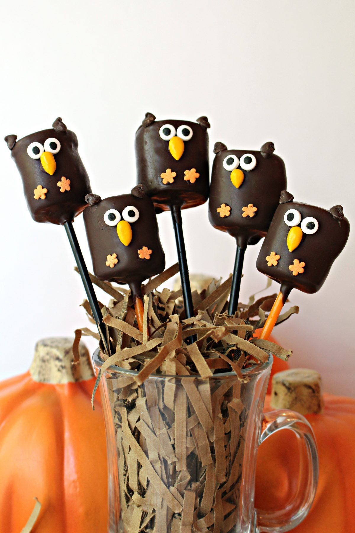 Five owl marshmallow pops on sticks in a cup filled with shredded paper like a nest.