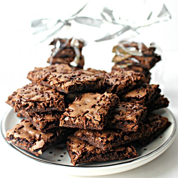 Piles of Malted Milk Brownie Bark on a white plate with two wrapped stacks of bark in the background