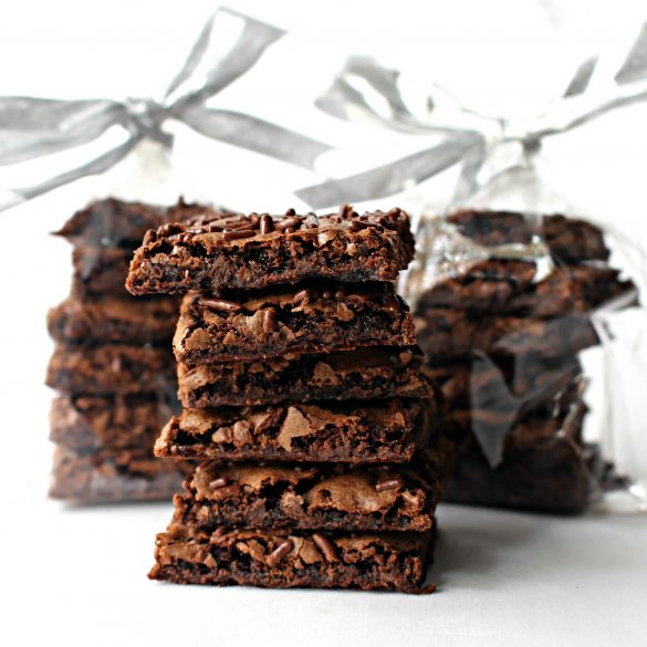 Three stacks of Malted Milk Brownie Bark. Two stacks are wrapped in cellophane bags with silver bows.