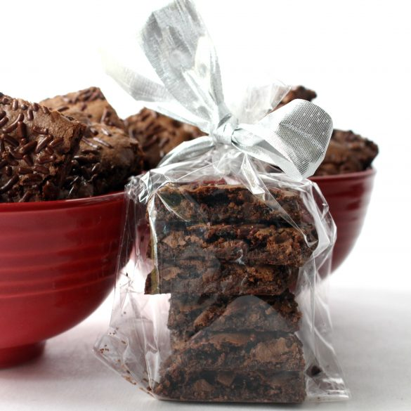 Wrapped stack of Malted Milk Brownie Bark with two red bowls in the background