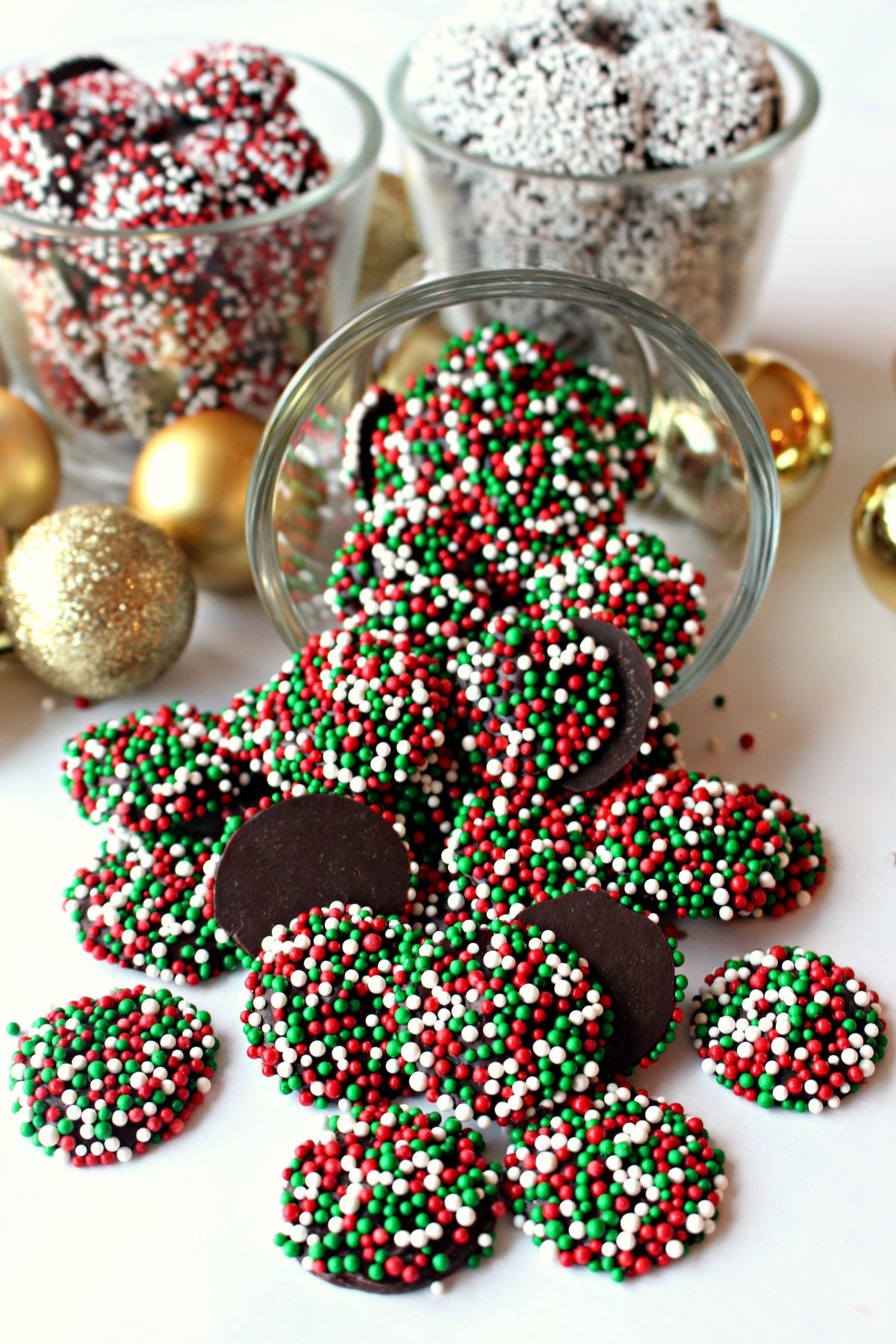A tipped clear glass spilling out red and green sprinkled chocolates.