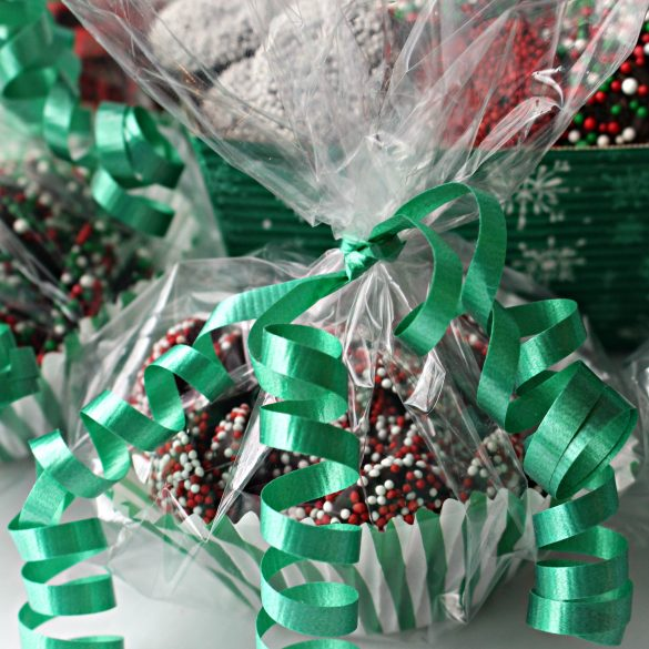 Nonpareil chocolates packaged for gifting in paper candy cups inside plastic bags tied with a green curling ribbon